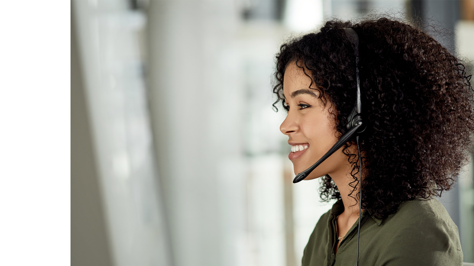Female contact center operator smiles while using a hand-free phone system