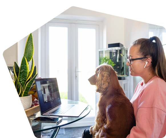 Young woman and her dog join a video call at home