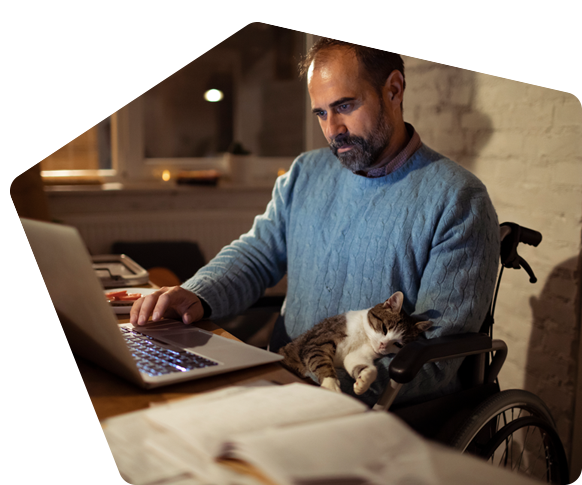 Man in wheelchair works from home with his cat