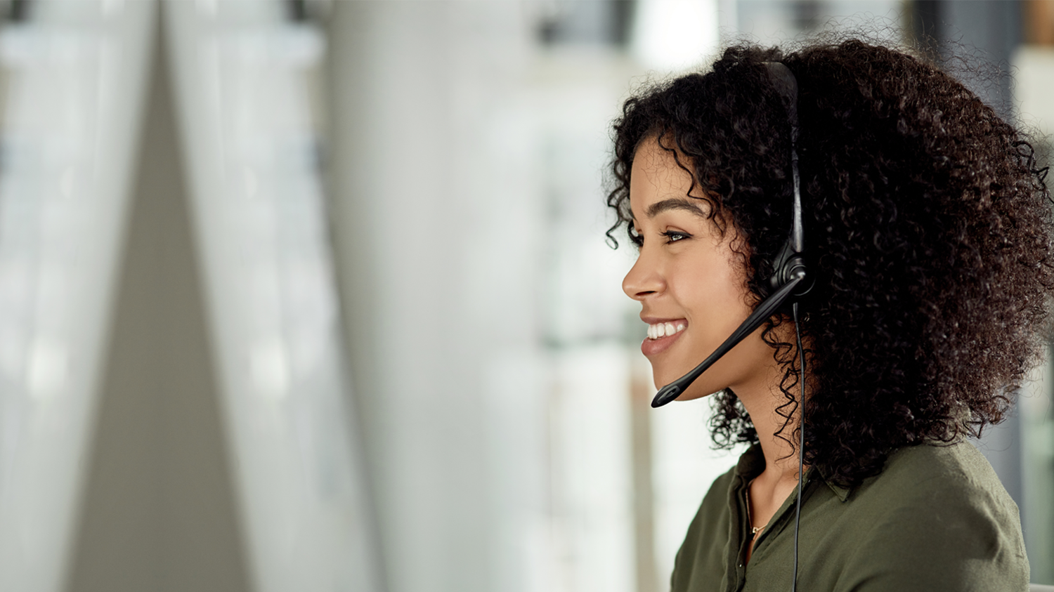 Woman with headset smiles while answering calls using Intrado's contact center solutions