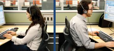 two call center operators sitting opposed each at their keyboard wearing a headset